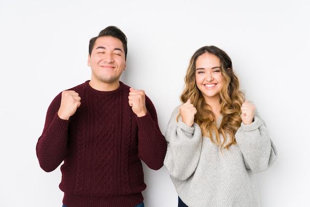 Jovem casal posando em uma parede branca, levantando o punho, sentindo-se feliz e bem sucedido. conceito de vitória.