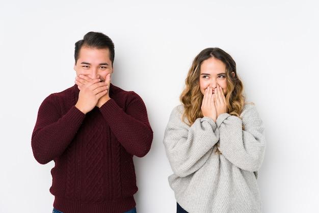 Jovem casal posando em uma parede branca rindo de algo, cobrindo a boca com as mãos.
