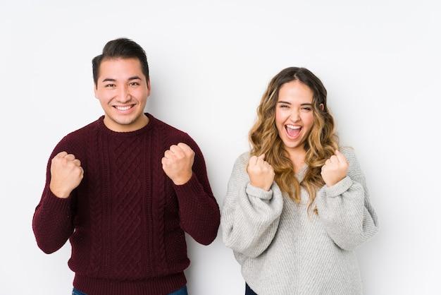 Jovem casal posando em uma parede branca torcendo despreocupado e animado. conceito de vitória.