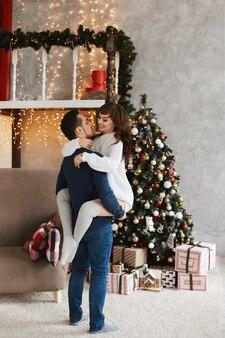 Jovem casal posando no interior da sala decorada para as férias de natal