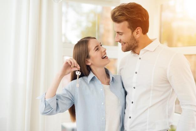 Jovem casal posando para uma foto em um quarto brilhante.