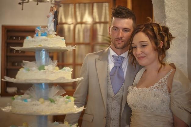 Jovem casal posando perto do bolo de casamento