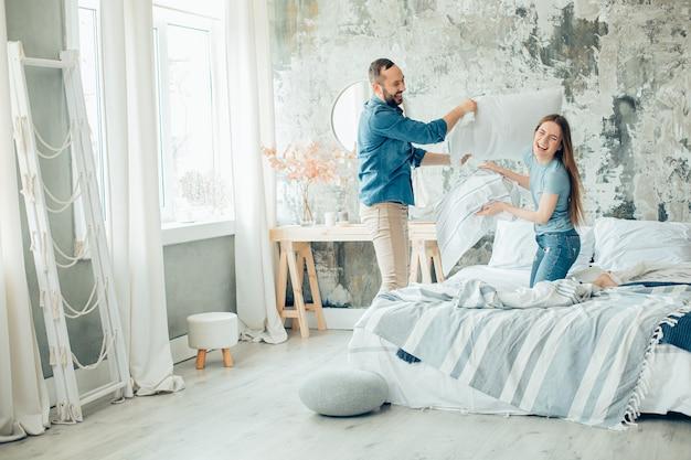 Jovem casal positivo se divertindo durante o isolamento e organizando uma luta de travesseiros em casa