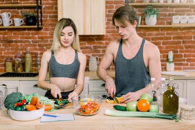 Jovem casal preparando a salada na cozinha. jovem e mulher de cabelos loiros, relaxar e se divertir com a culinária