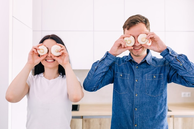 Jovem casal preparando o café da manhã na cozinha fecha os olhos com cogumelos rindo