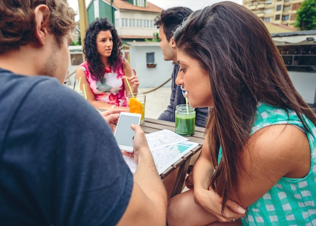 Jovem casal procurando um smartphone sentado à mesa com os amigos em um dia de verão ao ar livre