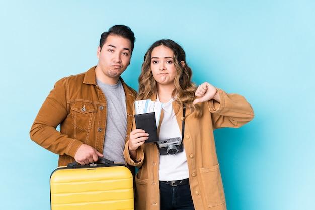 Jovem casal pronto para uma viagem, mostrando um gesto de antipatia, polegares para baixo