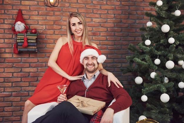 Jovem casal que encontra o natal que abraça em casa. ano novo. humor festivo de um homem e uma mulher