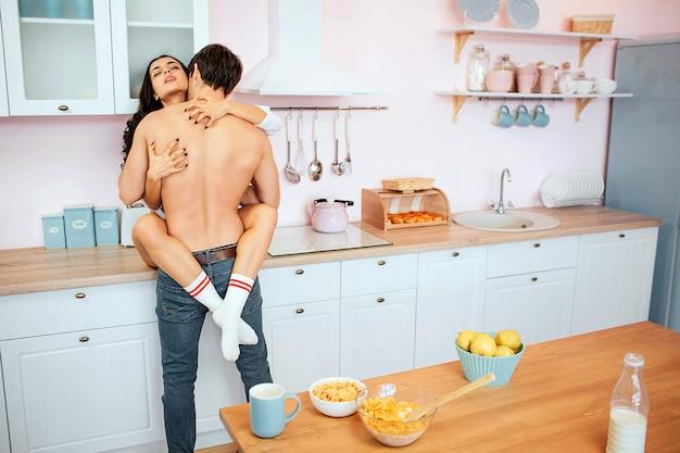 Jovem casal quente fazendo sexo no armário da cozinha. ela se senta lá e abraça o cara com pernas.