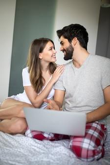 Jovem casal relaxando com o laptop em casa. conceito de amor, felicidade, pessoas e diversão.