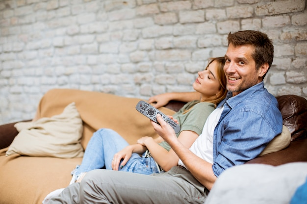 Jovem casal relaxando e assistindo tv em casa a sorrir