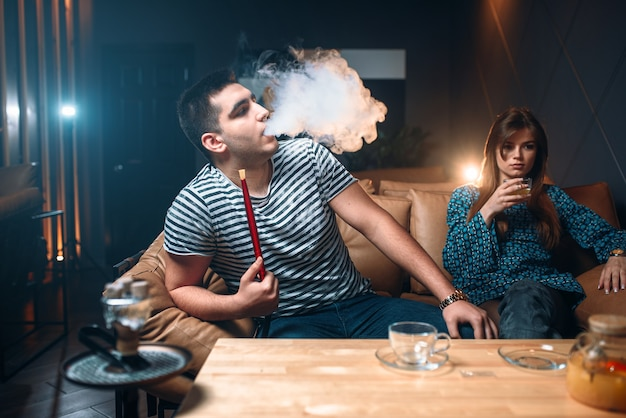 Jovem casal relaxando e fumando narguilé