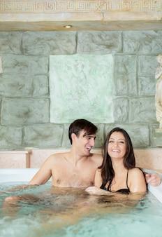 Jovem casal relaxando na banheira de hidromassagem