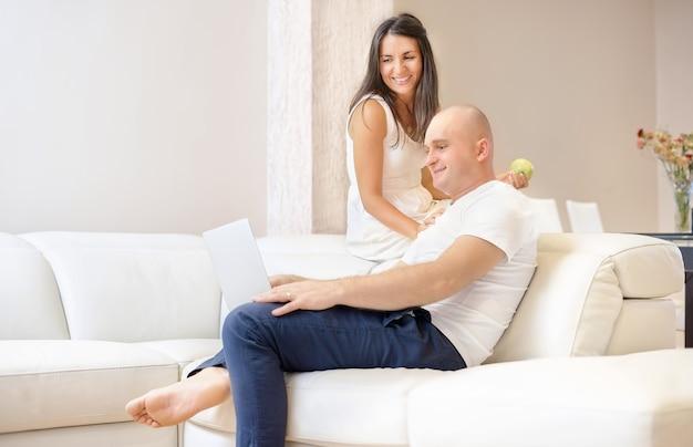 Jovem casal relaxando no sofá com o laptop. conceito de amor, felicidade, pessoas e diversão.