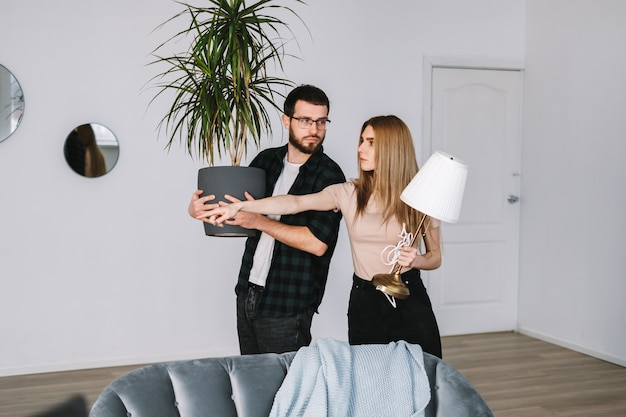 Jovem casal renovando sua nova casa e movendo móveis juntos.
