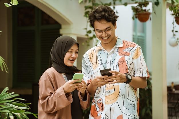 Jovem casal riu enquanto segura um telefone celular