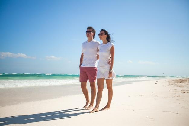 Jovem casal romântico andando na praia exótica em dia ensolarado