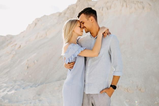 Jovem casal romântico ao ar livre, abraçando e quase beijando.