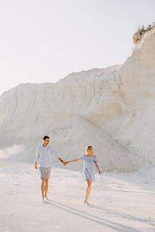 Jovem casal romântico ao ar livre, de mãos dadas e caminhando.