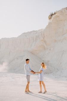 Jovem casal romântico ao ar livre, de mãos dadas e sorrindo.