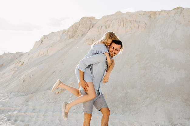 Jovem casal romântico ao ar livre. homem dando um cavalinho nas costas, ambos sorrindo.