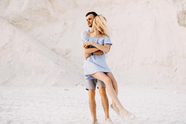 Jovem casal romântico ao ar livre se divertindo. homem girando mulher, sorrindo.