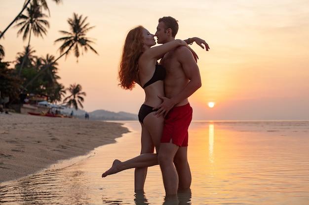 Jovem casal romântico apaixonado no pôr do sol feliz na praia de verão juntos se divertindo usando maiôs