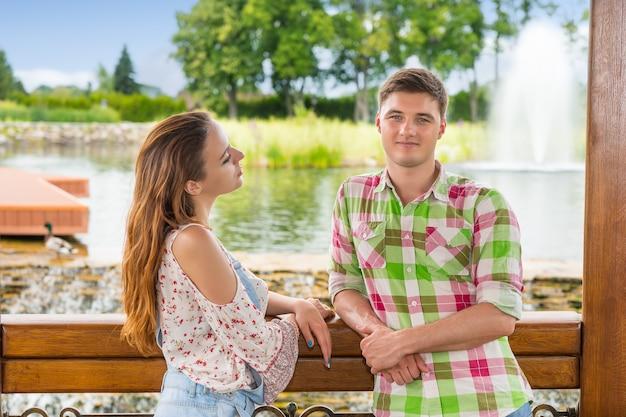 Jovem casal romântico apoiado na grade do gazebo de madeira em frente a uma cachoeira artificial em um parque com lago, fonte e diferentes árvores