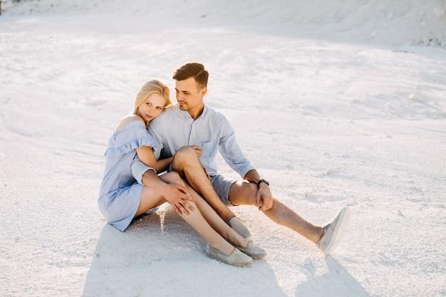 Jovem casal romântico calmo sentado na areia branca, se abraçando.