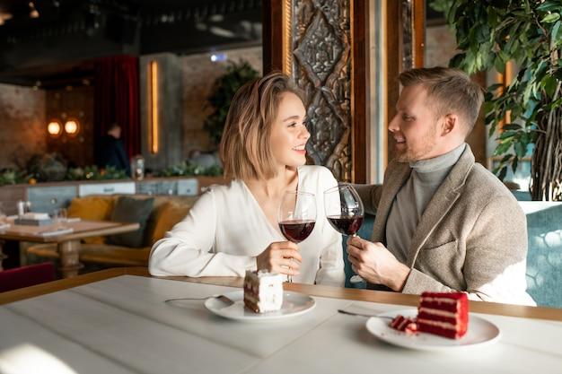 Jovem casal romântico com taças de vinho tinto conversando e fazendo torradas na mesa servida depois do almoço em restaurante luxuoso