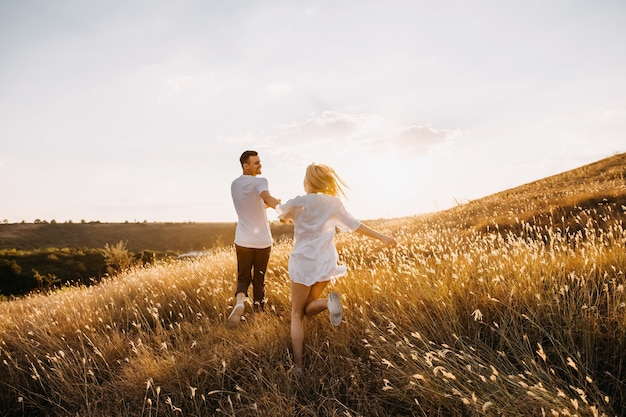 Jovem casal romântico correndo em um campo aberto com grama seca ao pôr do sol, de mãos dadas.