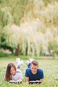 Jovem casal romântico deitado no parque e lendo livros