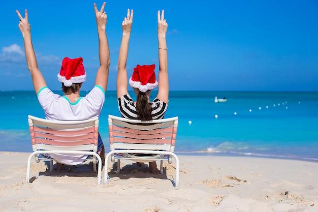 Jovem casal romântico em chapéus de papai noel durante as férias de praia