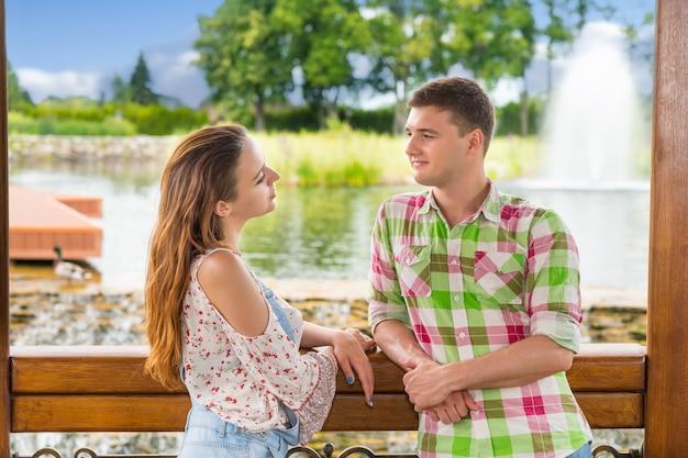 Jovem casal romântico encostado na grade do gazebo de madeira e olhando um para o outro em frente a uma cachoeira artificial em um parque com lago, fonte e árvores diferentes