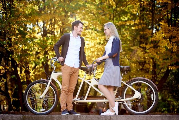 Jovem casal romântico feliz, homem barbudo e mulher atraente juntos na bicicleta dupla em tandem ao ar livre no parque ou floresta de outono
