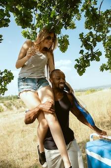 Jovem casal romântico internacional multiétnico ao ar livre no prado em um dia ensolarado de verão. homem afro-americano e mulher caucasiana fazendo piquenique juntos. conceito de relacionamento, verão.
