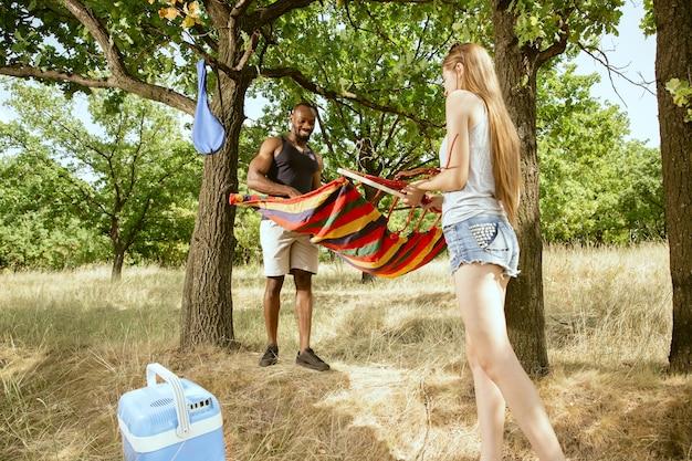 Jovem casal romântico internacional multiétnico ao ar livre no prado em um dia ensolarado de verão. homem afro-americano e mulher caucasiana se preparando para fazer um piquenique juntos. conceito de relacionamento, verão.