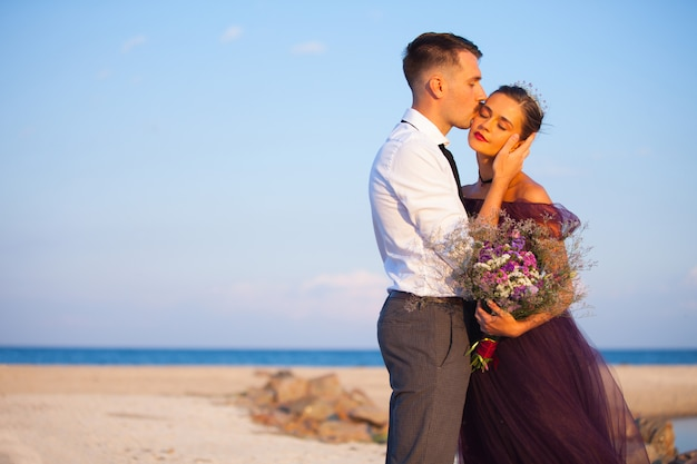 Jovem casal romântico relaxante na praia, assistindo o pôr do sol