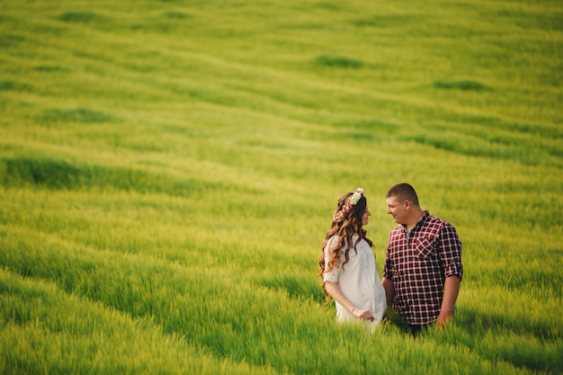 Jovem casal romântico romântico feliz na parede verde da natureza em dia de verão. mulher grávida esperando um bebê. futura mãe e pai, família. mãe, dia dos pais. copie o espaço