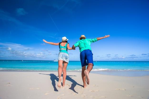 Jovem casal romântico se divertir na praia tropical do caribe