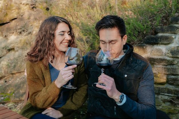 Jovem casal romântico sentado em um jardim, degustando uma taça de vinho tinto durante um piquenique.