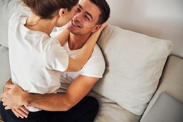 Jovem casal romântico sentado no sofá