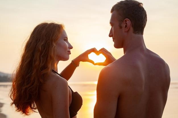 Jovem casal romântico sexy apaixonado feliz na praia de verão juntos se divertindo usando maiôs, mostrando o sinal do coração ao pôr do sol
