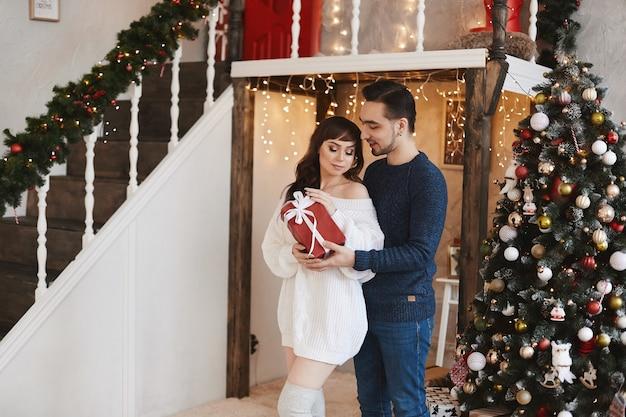 Jovem casal romântico trocando presentes de natal na sala de estar decorada para o feriado de ano novo