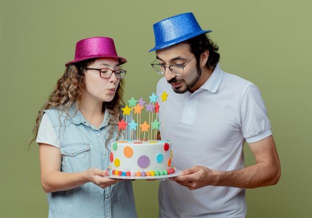 Jovem casal satisfeito com um chapéu rosa e azul, segurando e soprando um bolo de aniversário