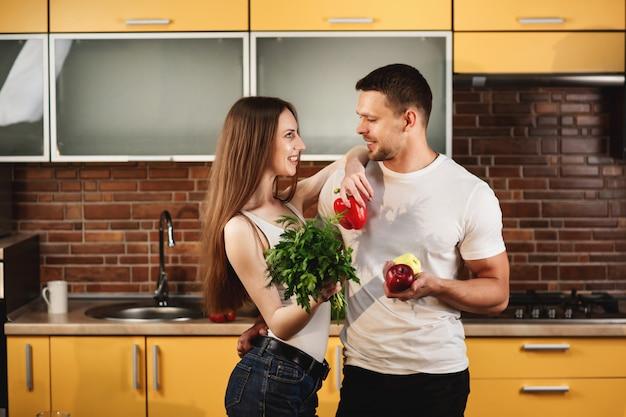 Jovem casal saudável e nutrição adequada. homem e mulher posando na cozinha segurando verduras e legumes. jovens se entreolham