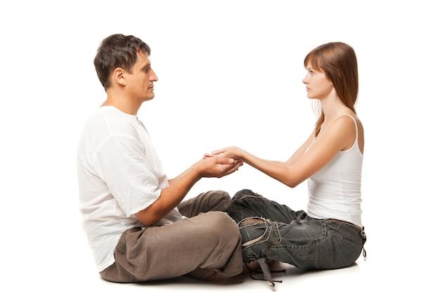 Jovem casal saudável em posição de ioga em fundo branco