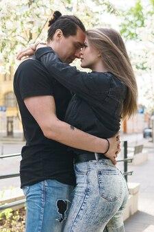 Jovem casal se abraçando durante um encontro ao ar livre