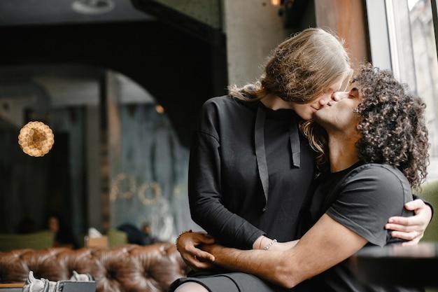 Jovem casal se abraçando e beijando em um café.