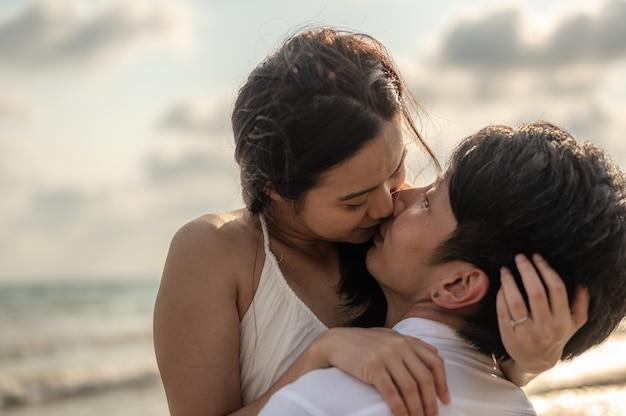 Jovem casal se abraçando e beijando na praia por do sol. verão apaixonado, conceito de dia dos namorados.